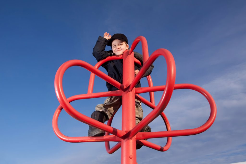 Stock Photo: 1418-648 Boy playing on a jungle gym in a park