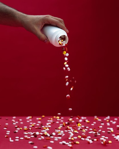 Stock Photo: 1422-740 Close-up of a human hand pouring pills from a bottle