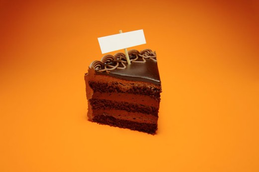 Close-up of a blank nameplate on a slice of a chocolate cake : Stock Photo