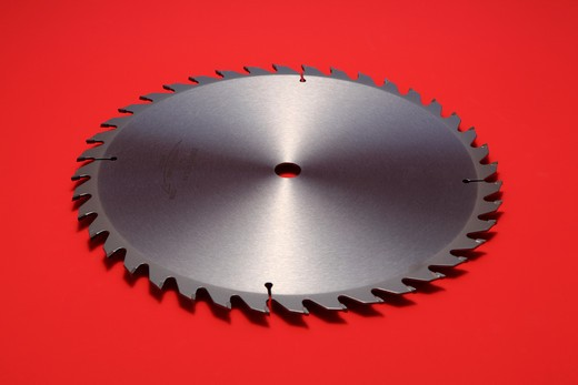 Stock Photo: 1422R-1151 Large circular metal blade with sharp teeth on red background