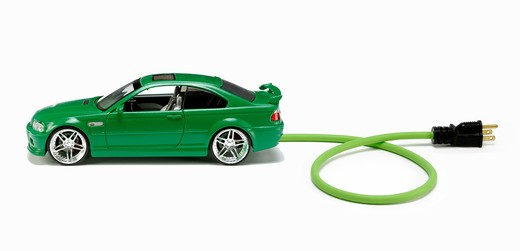 Stock Photo: 1422R-997 Small green automobile with a green electrical power cord and black plug