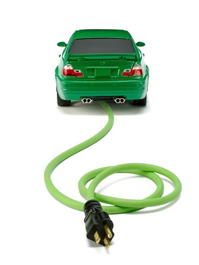 Stock Photo: 1422R-998 Small green automobile with a green electrical power cord and black plug