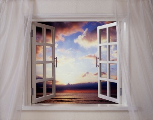 Sunset over the sea viewed through a window : Stock Photo