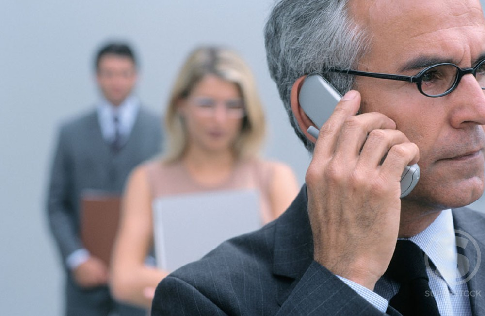 Businessman talking on a cell phone, two businesspeople in the background, blurred : Stock Photo