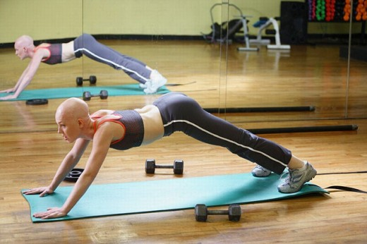 Caucasian woman with cancer/alopecia areata working out : Stock Photo