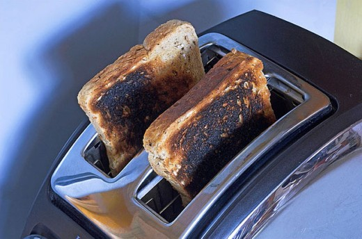 Stock Photo: 1436R-255343 Burnt toast in toaster burned