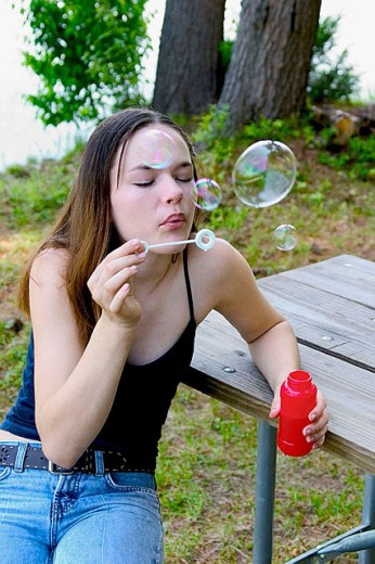 Teenage girl, sitting at a picnic table, blowing soap bubbles : Stock Photo