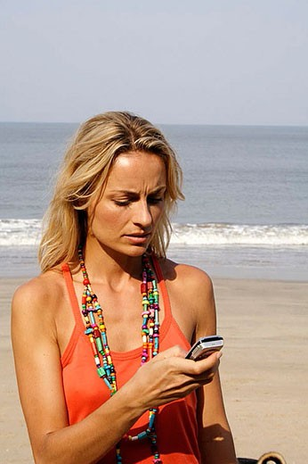 Beautiful blonde woman looking upset at a phone on an beach in India. : Stock Photo