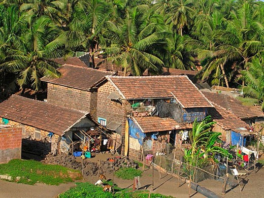 Stock Photo: 1436R-266809 Traditinal houses of Fishermen's with sloping roofs made of manglori tiles and coconut cocos nucifera palms near Mandavi channel from Thiba palace  Ratnagiri, Maharashtra, India