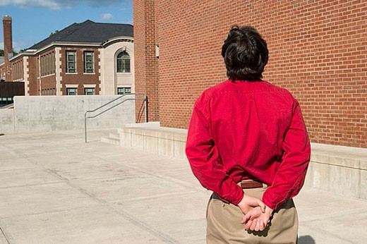 Man, his hands behind his back, standing outside on a concrete walkway : Stock Photo