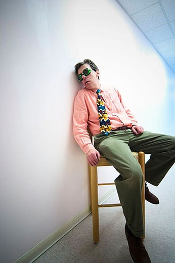 Man wearing goggles and a tie, sitting in a chair next to a white wall : Stock Photo
