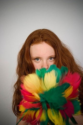 Stock Photo: 1436R-275138 Long red_hair teen girl holding a feather duster