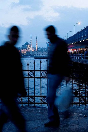 Stock Photo: 1436R-278815 People crossing Galata bridge and Yeni mosque in background in the evening, Istanbul. Turkey
