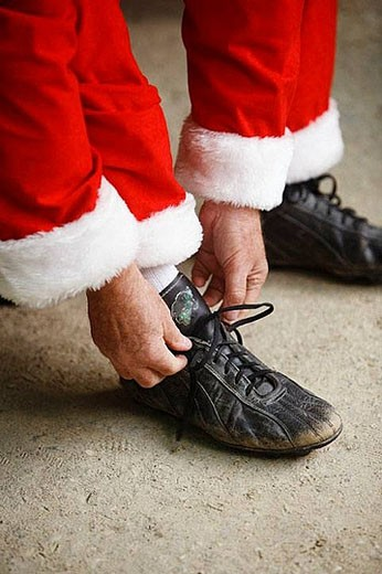 Santa putting on baseball shoes : Stock Photo