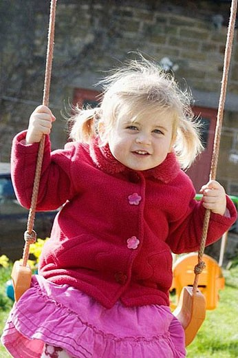 Stock Photo: 1436R-279853 3 year old girl swinging outside, smiling into camera, with bunches