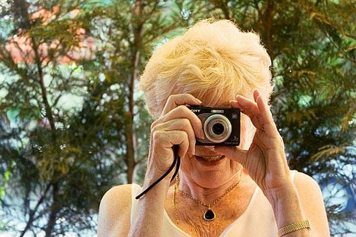 Stock Photo: 1436R-279926 glamorous, 70 year old lady taking a photo of the photographer, smiling