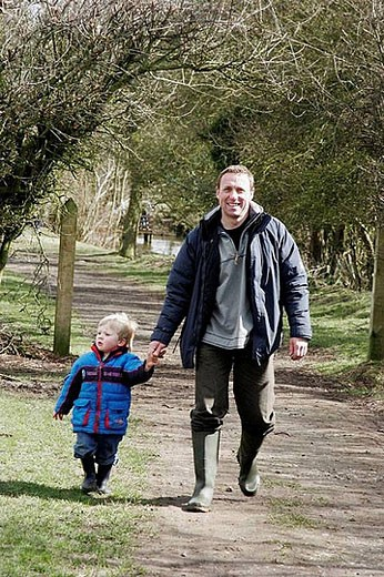 45 year old man walking in the park, with his 3 year old son : Stock Photo
