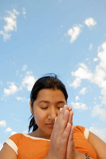 23 year old latina woman with hands folded while in prayer : Stock Photo