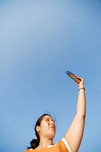 Stock Photo: 1436R-282055 23 year old latina woman with arm extended above head holding a Bible