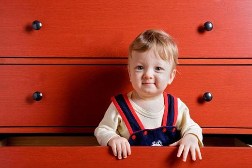 Baby boy playing inside cupboard drawer : Stock Photo