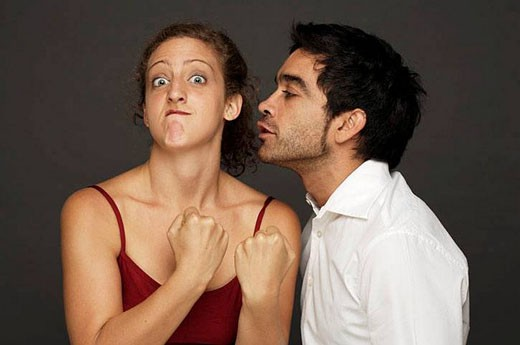 Man tries to kiss woman while she reacts in fight mode : Stock Photo