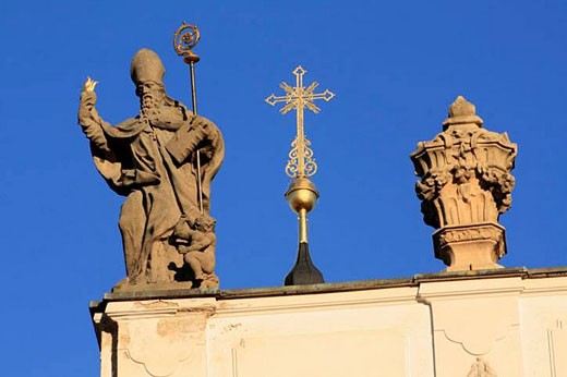 Baroque sculpture by Johann Anton Quitanainer of a Bishop ornaments the roof of the Church of the Assumption in Strahov Monastery. Czech Republic : Stock Photo