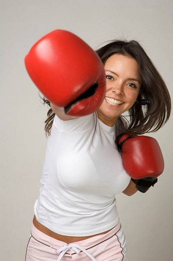 Latin woman wearing boxing gloves throwing punch at the camera : Stock Photo