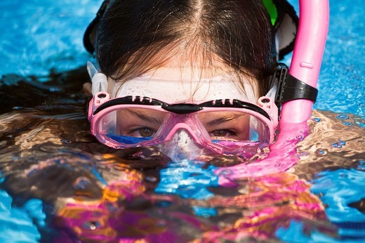 Stock Photo: 1436R-298254 Close-up of young girl wearing dive mask while snorkeling