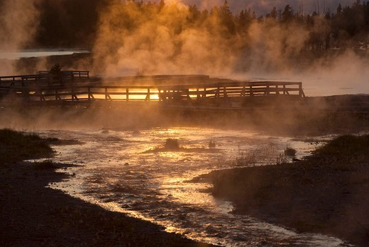 The setting sun reflecting on Firehole Lake geothermal area and boardwalk suggests a boiling pool of magma below : Stock Photo