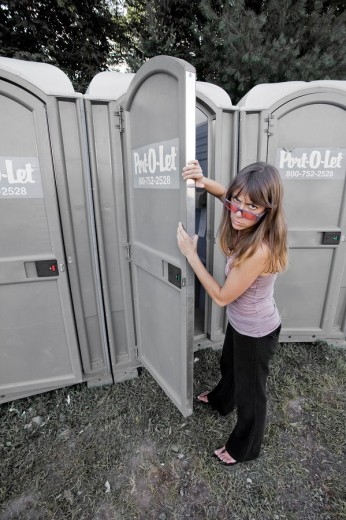 Young woman about to enter a portable toilet : Stock Photo