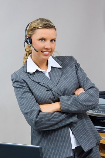 Caucasian businesswoman / secretary in her early 30s talking on a headset : Stock Photo