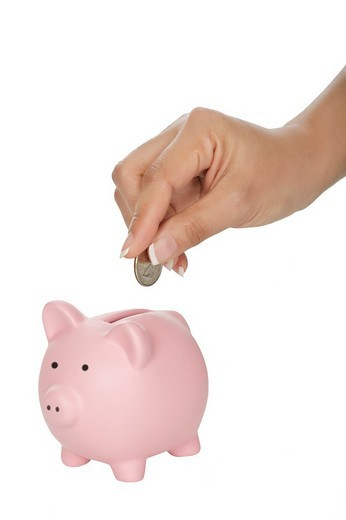 Woman placing a quarter into a piggy bank isolated on a white background : Stock Photo