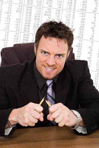 Caucasian businessman setting at a desk and looking very angry and frustrated because of the Stock Market : Stock Photo