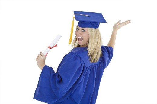 A female caucasian with blond hair standing in blue graduation gown and smiling  She is on a white background : Stock Photo