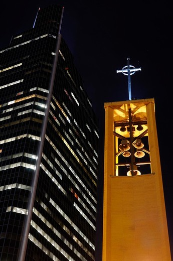 Bell Tower of Saint Olaf Catholic church with Campbell Mithum highrise tower in Minneapolis at night : Stock Photo