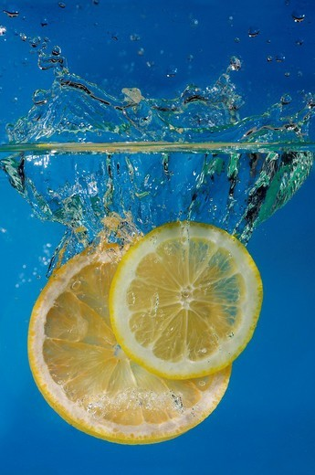 Lemon and grapefruit slices splashing into water with a blue background : Stock Photo