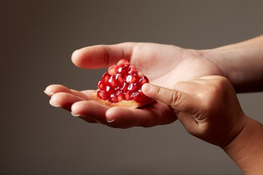 Stock Photo: 1436R-301508 Woman hand holding a red piece of pomegranate on grey background with child hand touching it