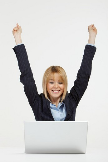 Happy blonde business woman working in office with laptop raising hands for victory : Stock Photo