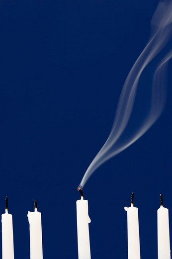 Stock Photo: 1436R-303689 Five white candles that have just been blown out, with smoke rising from the center candle against a blue background  The wick is still red hot