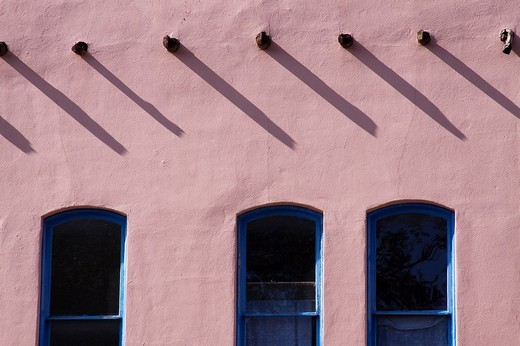 Stock Photo: 1436R-304137 Vigas casting shadows over three windows of a building in the Pueblo revival style of architecture in Santa Fe, New Mexico