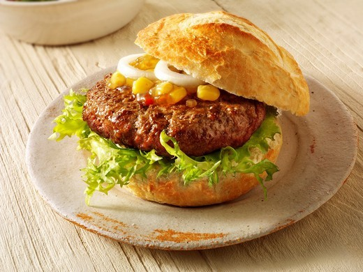 Home made burger in a crusty roll with sweetcorn relish and omion : Stock Photo