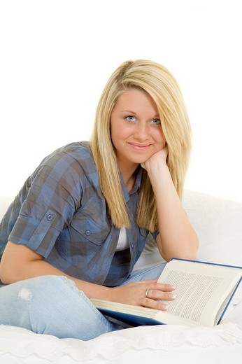 Beautiful Caucasian teenager setting in bed reading a book : Stock Photo