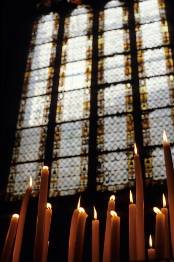 Stock Photo: 1436R-306920 France auch burning candles inside sainte marie cathedral with moles stained glass window in the background