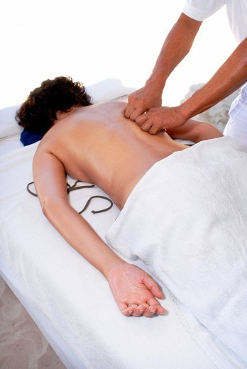 Stock Photo: 1436R-308045 A man practicing a deep tissue massage with his knuckles on a woman's back