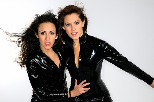 Two young women with blowing hair in full body black plastic catsuits on white background : Stock Photo