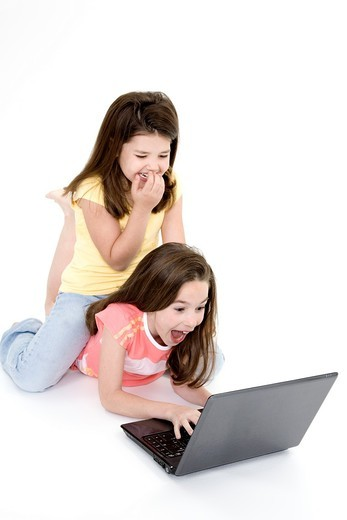 Sisters playing on a laptop computer on a white background : Stock Photo