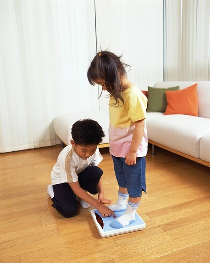 Stock Photo: 1436R-318916 A small girl standing on scale while her brother presses button