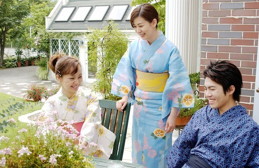 Three people in kimono talking in garden : Stock Photo
