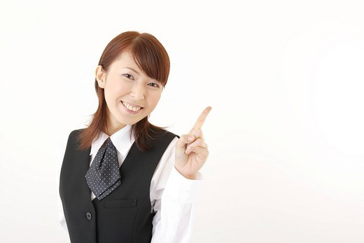 A woman in formal attire pointing a direction : Stock Photo