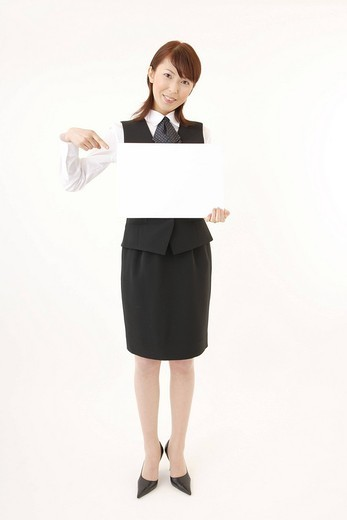 A woman in formal attire holding a blank message : Stock Photo